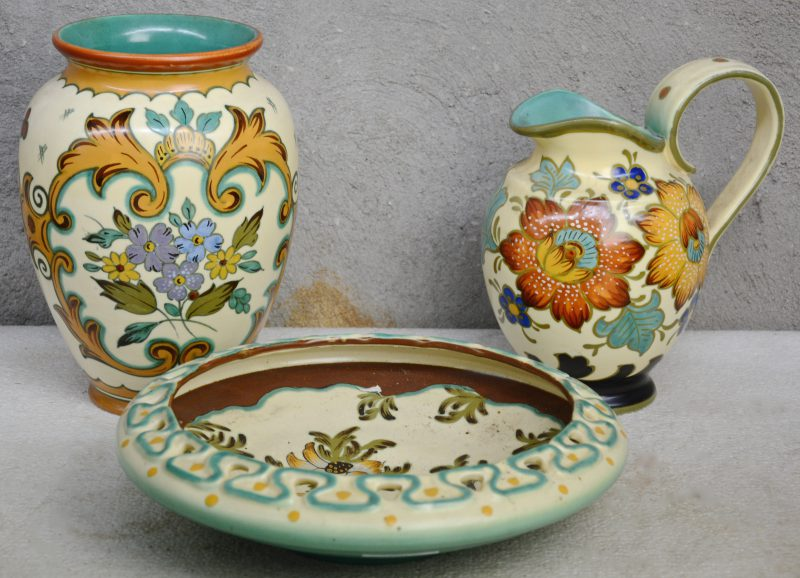 Een lot Gouds plateel met meerkleurige bloemendecors, bestaande uit een vaas, een schenkkan en een diepe schotel met opengewerkte rand.