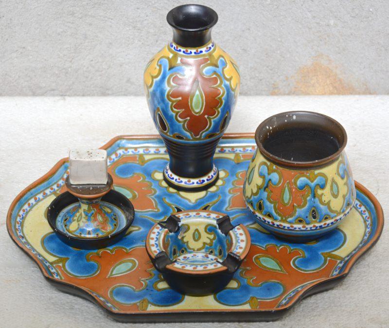 Een potje, een vaasje, een asbak en een luciferhouder van meerkleurig Gouds aardewerk op bijpassende schotel. Decor 'Emmy'. Omstreeks 1925. Gaaf.
