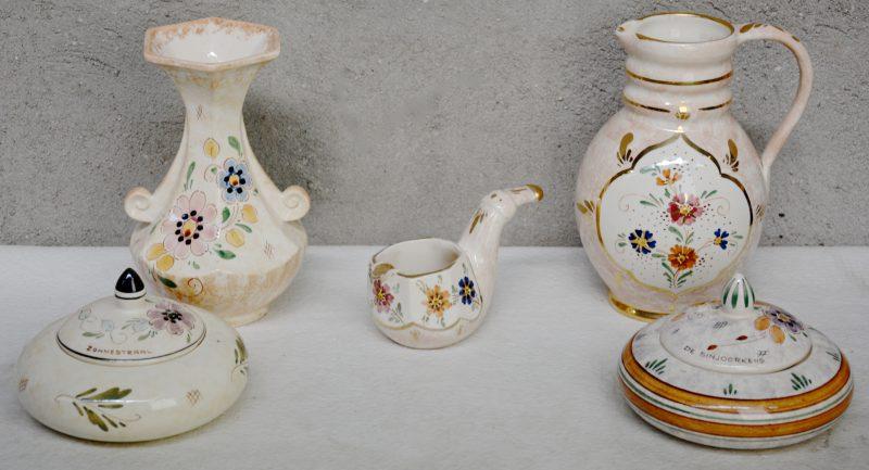 Twee dekseldoosjes, een vaas, een schenkkan en een pijpvormige asbak van glanzend plateel met meerkleurige decors.. Onderaan gemerkt.