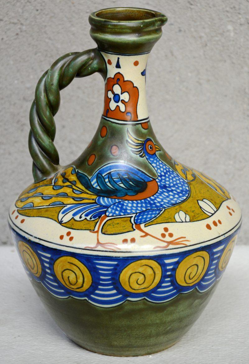 Een aardewerken sierkruik met gevlochten handvat, versierd met een meerkleurig decor van pauwen. Decor 505 met decorateursmonogram 'A.P.'. Tijdperk art deco.