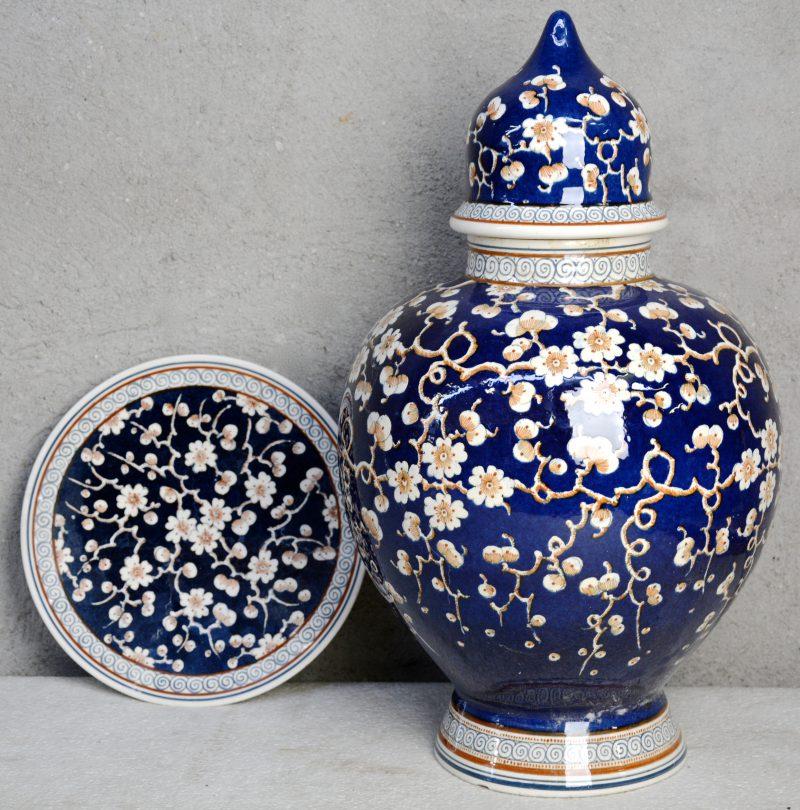 Een grote bolle dekselvaas en een wandschotel van glanzend plateel met een meerkleurig decor van bloesems op blauwe fond. Onderaan gemerkt. Gaaf.