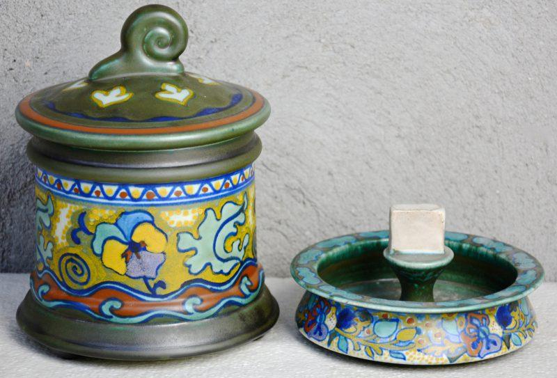 Een tabakspot en een asbak met luciferdoosjeshouder van meerkleurig plateel met mat glazuur. Respectievelijke decors 'Penseo' & 'Corona'. Gaaf. Jaren '20.