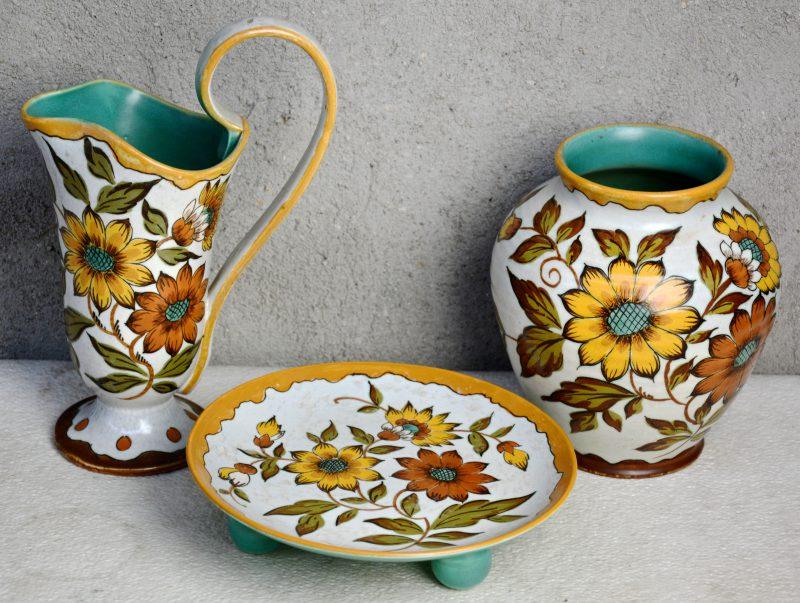 Een lot meerkleurig plateel met decor 'Fanny', bestaande uit een vaas, een sierkan en een schotel op drie bolle pootjes. Allen gemerkt. Gaaf.