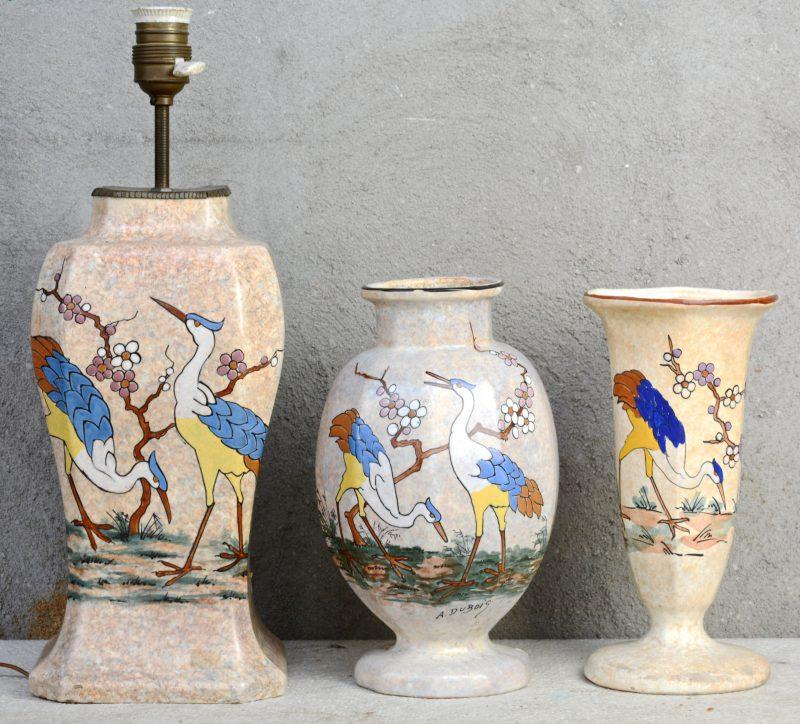 Twee vazen en een lampvoet van aardewerk met een meerkleurig decor van reigers in bloesems door Antoine Dubois. Gesigneerd en gemerkt.