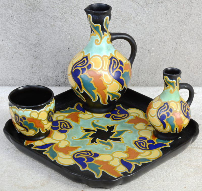 Een ensemble van meerkleurig plateel met decor 'Argos', bestaande uit twee kannetjes en een potje op een vierkante schotel. Onderaan gemerkt.