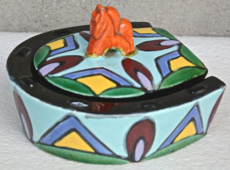 Een hoefijzervormig dekseldoosje van meerkleurig aardewerk, het deksel getooid met een paardje.  Onderaan gemerkt.