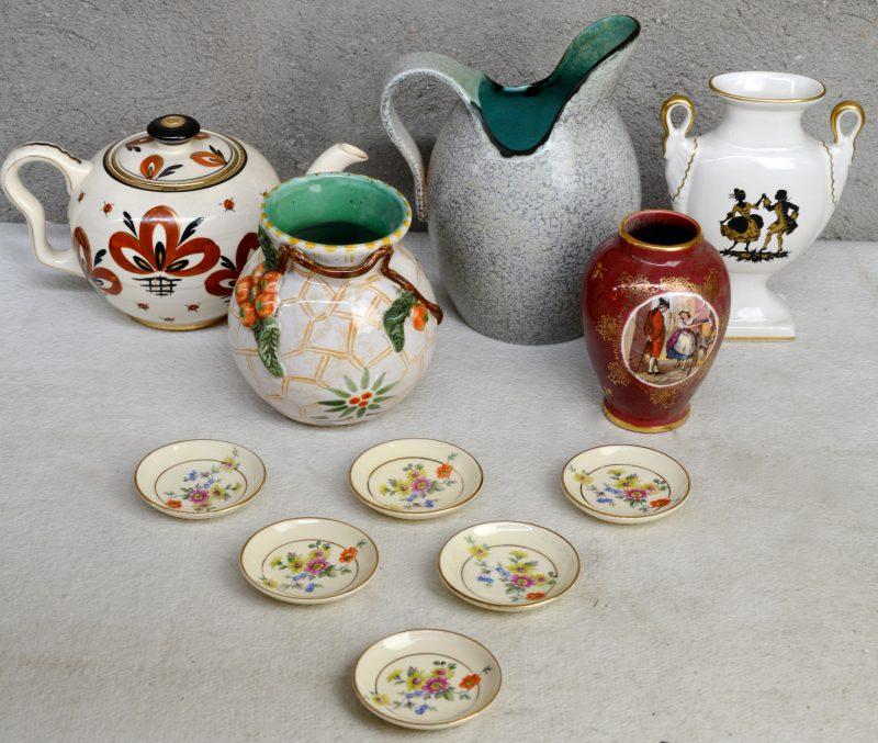 Een lot meerkleurig Gouds plateel met glanzend glazuur, bestaande uit een theepot, zes kleine schaaltjes, een vaas met reliëfdecor van sinaasappels, een vaasje in de stijl van Limoges, een plat siervaasje en een schenkkan. Allen gemerkt onderaan.