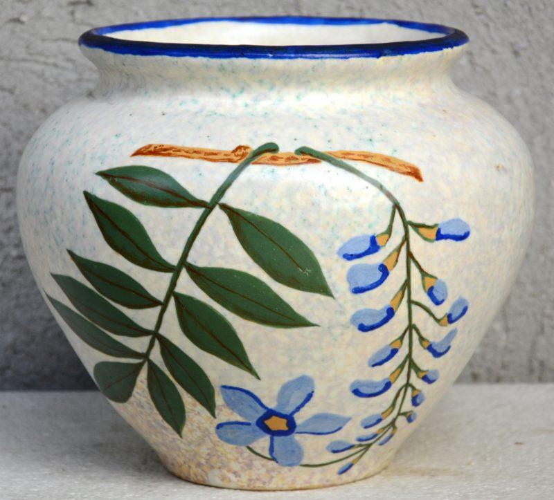 Een aardewerken jardinière met meerkleurig bloemendecor.