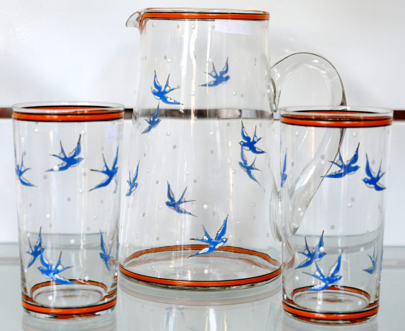 Een schenkkan met twee glazen, versierd met zwaluwen.