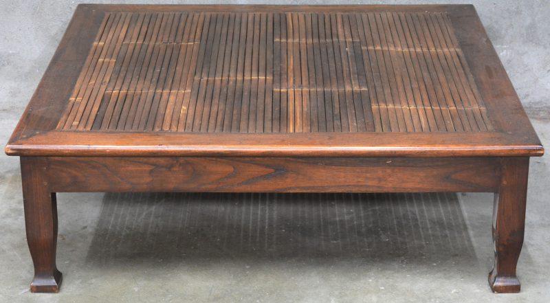 Een vierkante salontafel met een blad van bamboe.