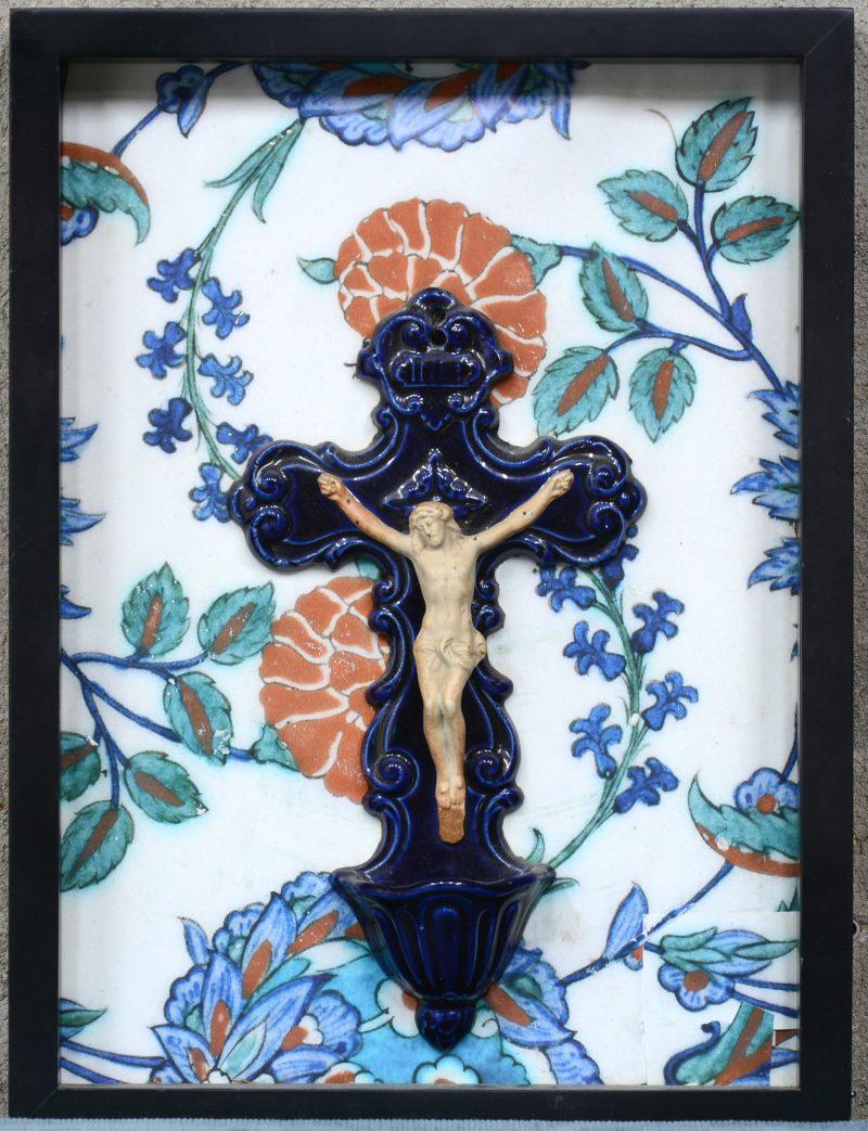Een geglazuurd aardewerken wijwatervat in de vorm van Christus aan het kruis.