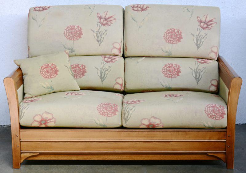 Een vintage kersenhouten tweezits bank met losse linnen kussens met een bloemenmotief.