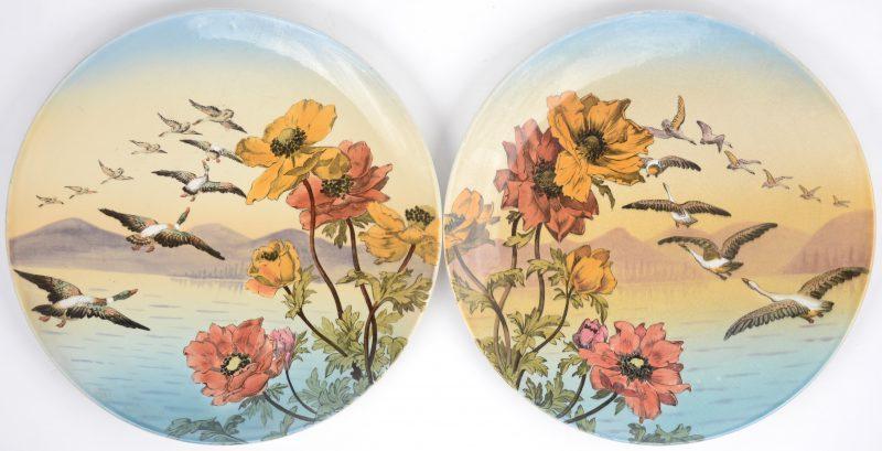 Twee grote aardewerken sierschotels met meerkleurig decor van ganzen. Decors 102 A & B. Achteraan gemerkt.