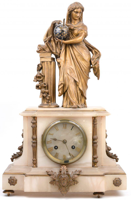 Een albasten schouwpendule, versierd met zamakken sierelementen en bovenaan getooid met een allegorisch beeld. Slinger, sleutel en een pootje manco. Op te knappen. XIXe eeuw.
