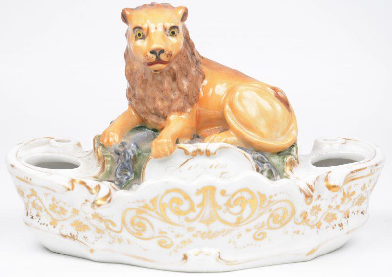 Een inktstel van Brussels porselein, versierd met vergulde motieven en getooid met een gepolychromeerde liggende leeuw met eronder de Belgische wapenspreuk. XIXe eeuw. Zonder recipiënten.