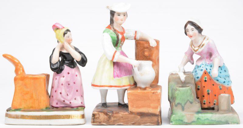 Drie groepjes als inktstelletjes van meerkleurig porselein, waarbij één in de vorm van een vrouw bij de waterpomp, één in de vorm van een strijkende vrouw en één in de vorm van een vrouw die zich opmaakt. XIXe eeuw.