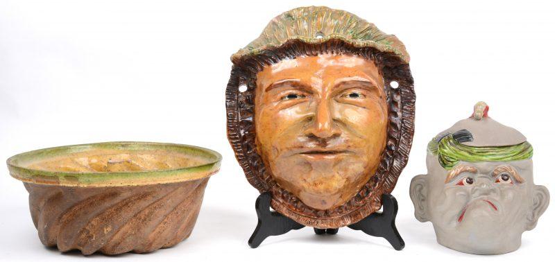 Een lot meerkleurig aardewerk, bestaande uit een wandjardinière in de vorm van een mannenhoofd, een tabakspot in de vorm van een karakterkop en een XIXe eeuwse puddingtulband.