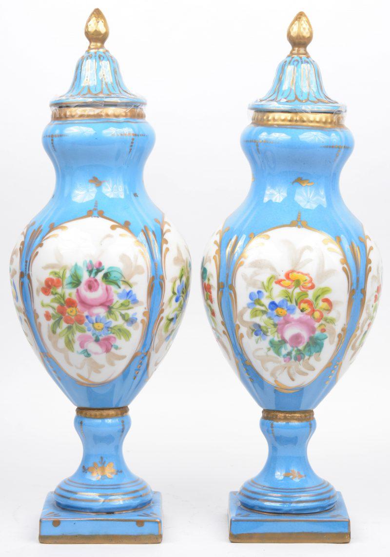 Twee dekselvazen van Frans porselein, versierd met een meerkleurig bloemendecor in cartouches op blauwe fond en het geheel afgewerkt met vergulde motieven.
