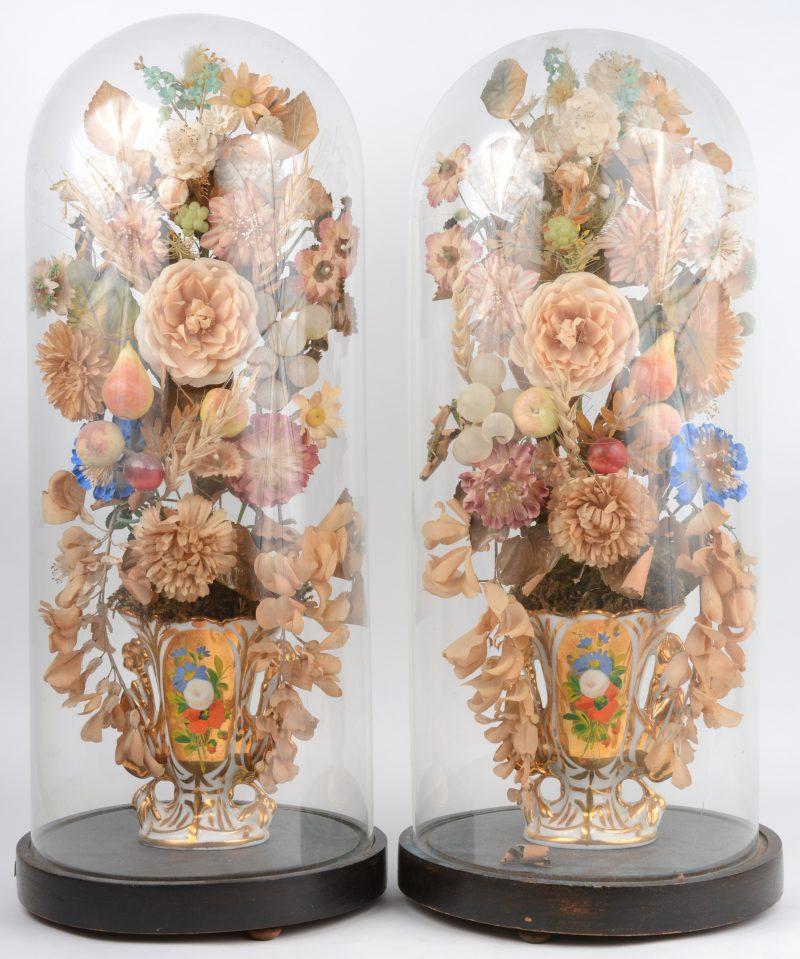 Een paar XIXe eeuwse hoornvaasjes van verguld Brussels porselein onder stolpen. Eén stolp gebarsten.