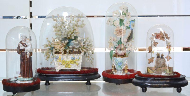 Vier verschillende glazen stolpen op houten sokkels, waarbij één met een hoornvaasje en één met een beeltenis van St. Antonius van Brussels porselein.