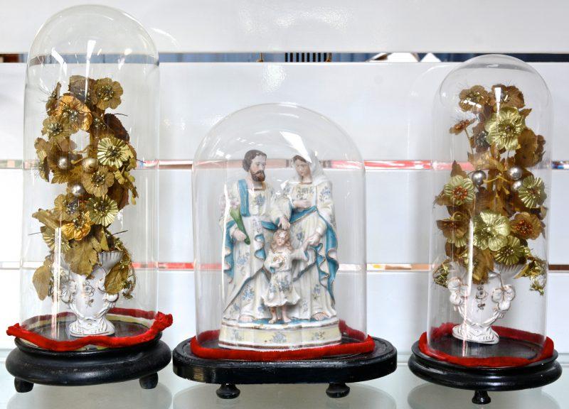 Een set van drie glazen stolpen met twee porseleinen vaasjes en een Heilige Familie van biscuit.