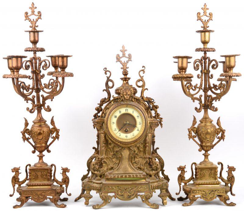 Messingen klokstel. Driedelig met pendule en twee kandelaars. Einde XIXde eeuw.
