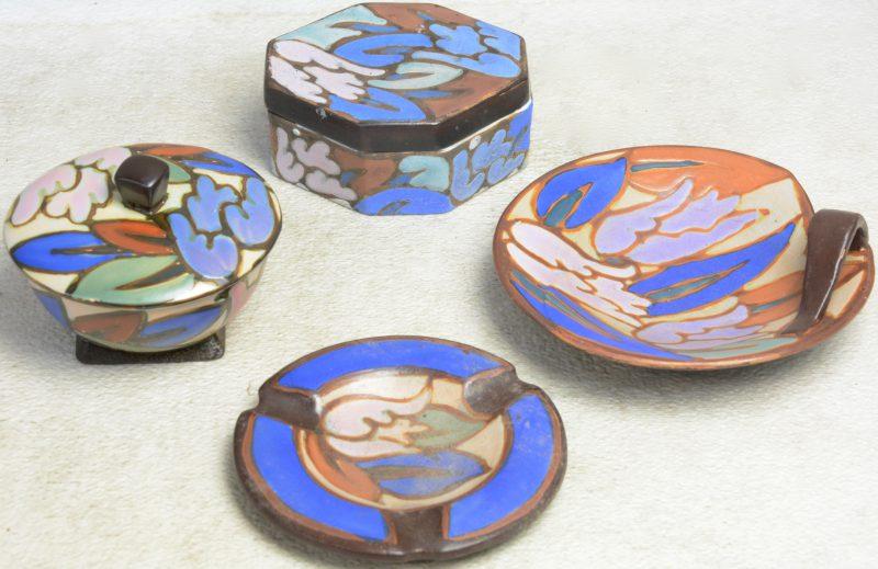 Een lot meerkleurig aardewerk, bestaande uit een zeshoekige dekseldoos een rond dekselporje, een aasbak en een vide-poche. Onderaan gemerkt.