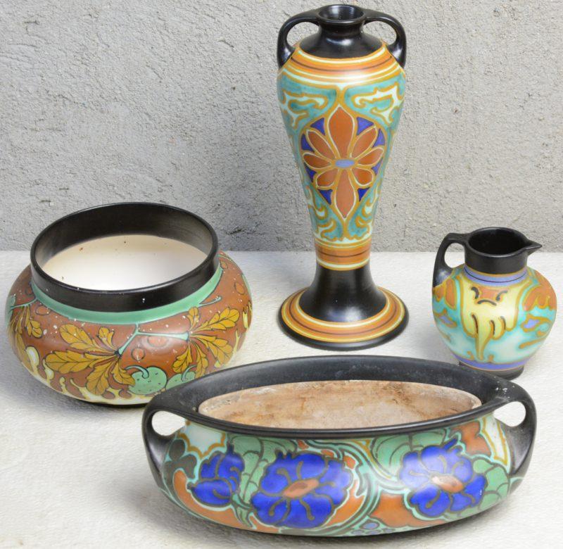 Een lot meerkleurig plateel, bestaande uit een jardinière met decor 'Jaargety', een lage vaas met decor 'Kastanje', een kannetje met decor 'Carel' en een hoog vaasje met decor 'Segal'. Allen gemerkt onderaan.