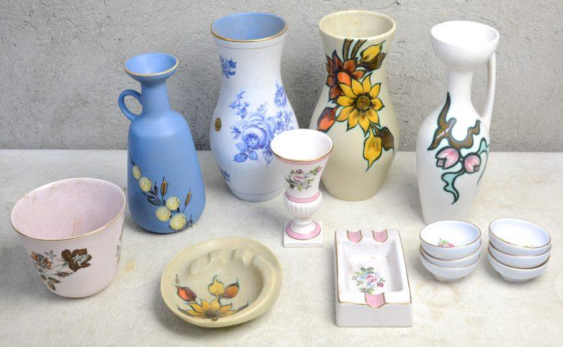 Een lot Gouds aardewerk met meerkleurige decors, bestaande uit zes kleine kommetjes, een bloempot, twee asbakken, twee sierkruiken, twee vazen en een vaasje op voet. Onderaan gemerkt.