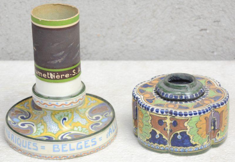"""Een inktpot en een luciferhouder van meerkleurig plateel, waarbij de tweede in opdracht van de """"Fabriques Belges d'Allumettes, Bruxelles"""". Onderaan gemerkt."""