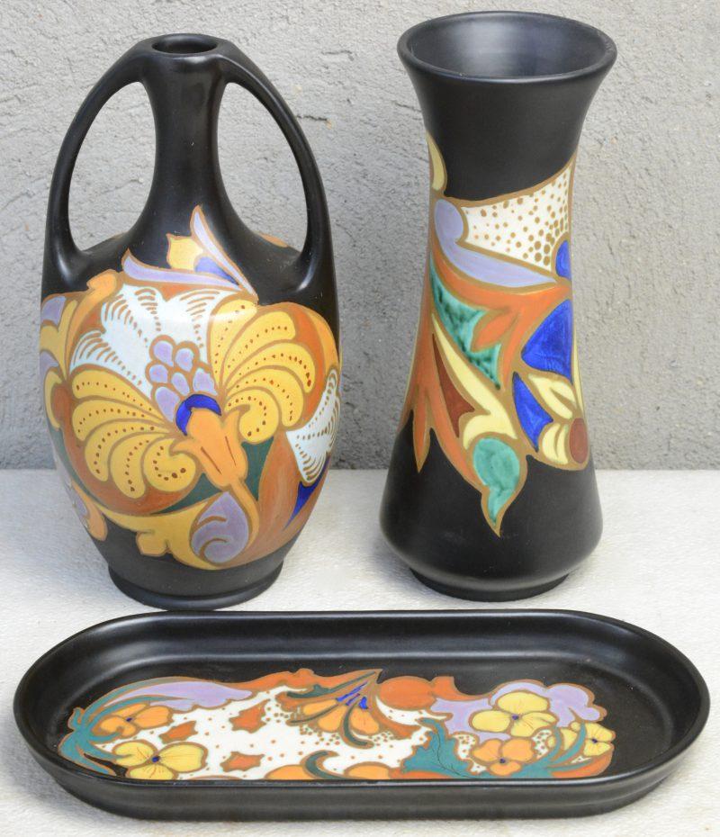 Twee vazen en een schotel van meerkleurig plateel in de stijl van Gouda. Onderaan gemerkt.