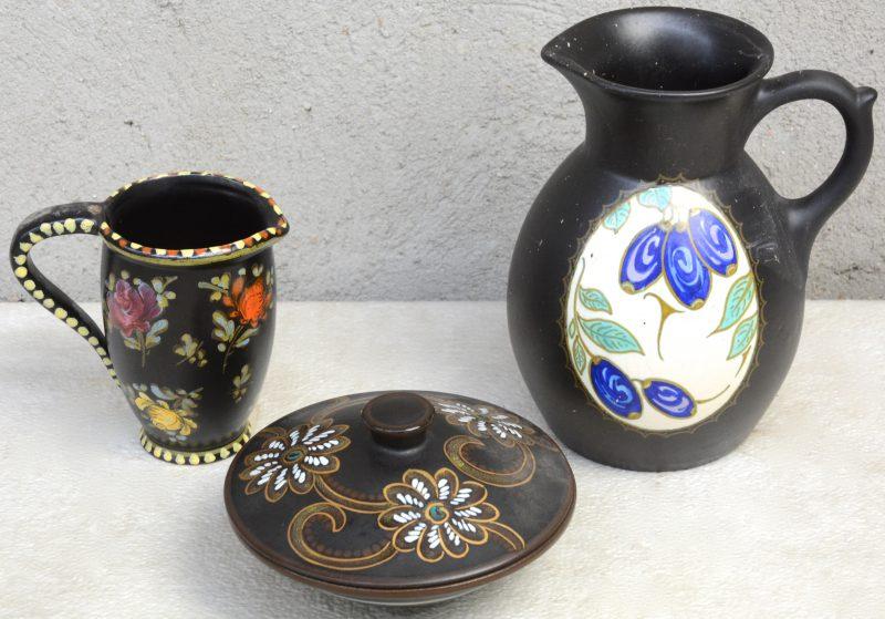 Twee schenkkannen en een bonbonnière van Gouds plateel met meerkleurige decors op zwarte fond. Onderaan gemerkt.