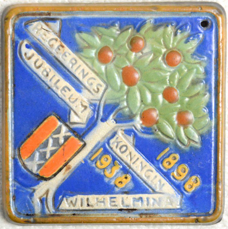 Een gepolychromeerde herdenkingstegel naar aanleiding van, het veertigjarig regeringsjubileum van Koningin Wilhelmina in 1938. Achteraan gemerkt.