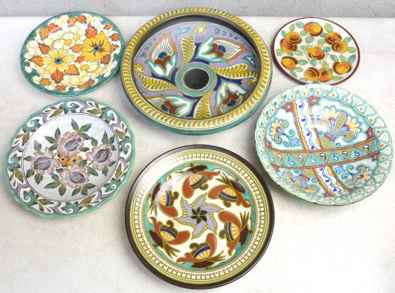 Een lot van zes schotels van Gouds plateel met meerkleurig decors, waarbij één met geajoureerde rand. Onderaan gemerkt.