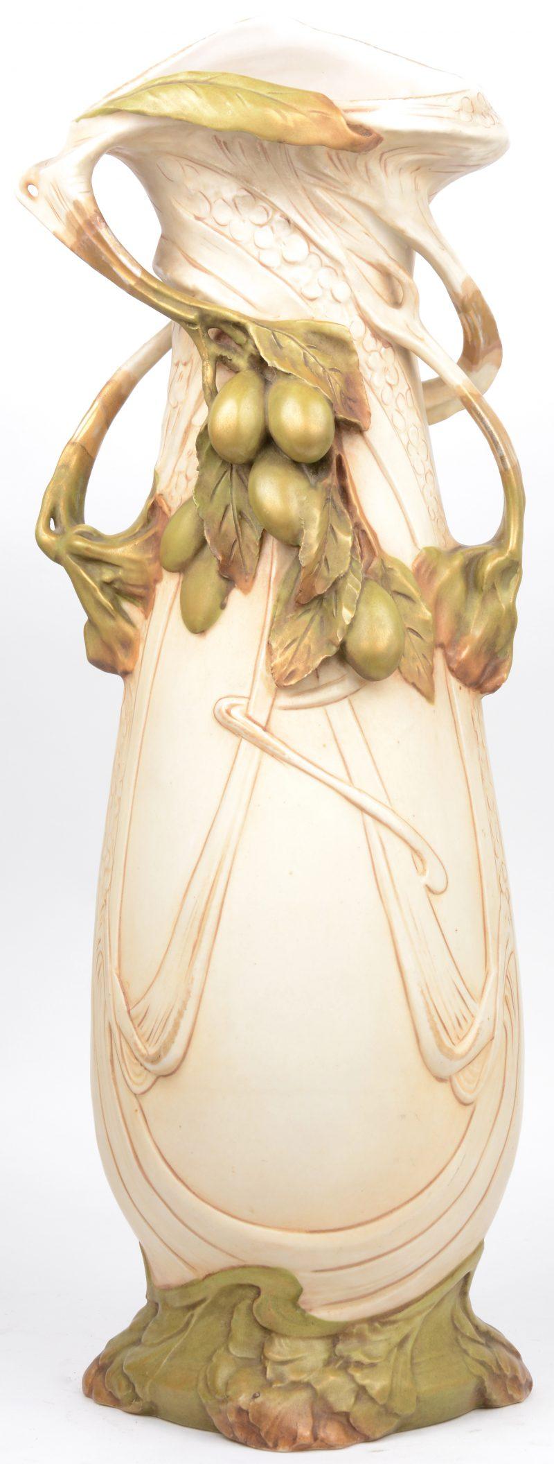 Een art nouveau siervaas van gepolychromeerd porselein met versieringen van bladeren en vruchten in hoogreliëf. Onderaan gemerkt.