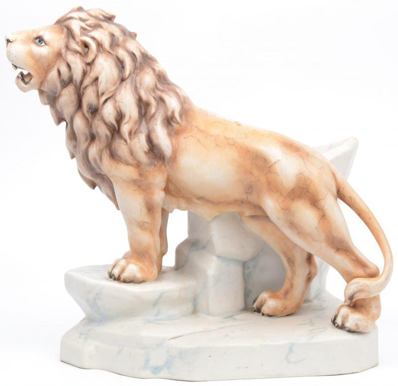 Een siervaas van meerkleurig porselein in de vorm van een leeuw op een rots. Mogelijk Amphora.