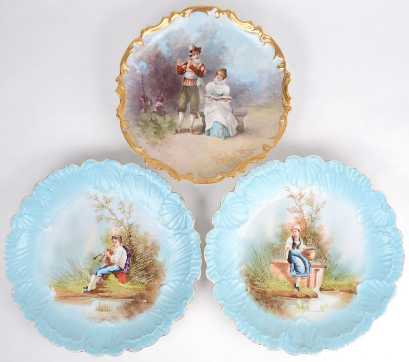 Drie laat XIXe eeuwse sierschotels met handgeschilderde decors en vergulde randen, waarbij er twee een paar vormen. Het enkele gesigneerd 'Dubois'.