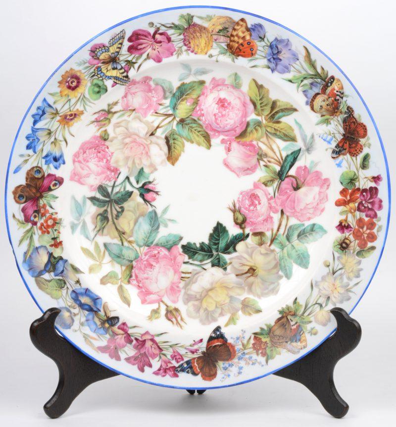 Een grote porseleinen sierschotel met een handgeschilderd decor van bloemen en vlinders. Randschilfer.