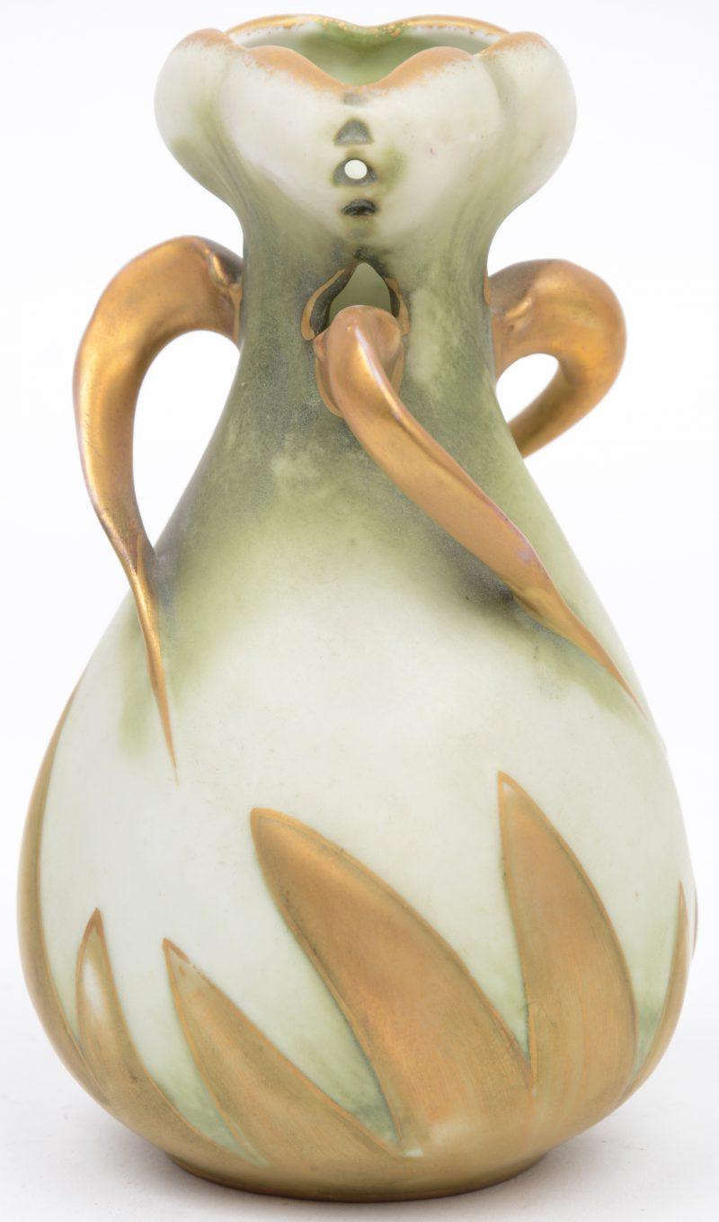 Een art nouveau vaasje van meerkleurig porselein met veeguld reliëfdecor. Onderaan gemerkt.