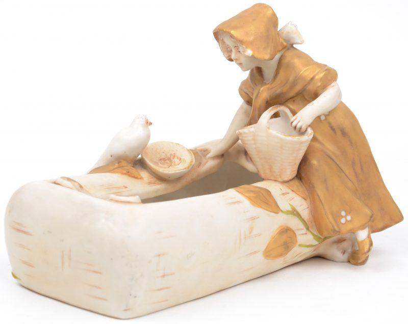 Een kleine sierjardinière van deels verguld porselein, versierd met een meisje met mand en een vogel. Onderaan gemerkt. Tijdperk art nouveau.