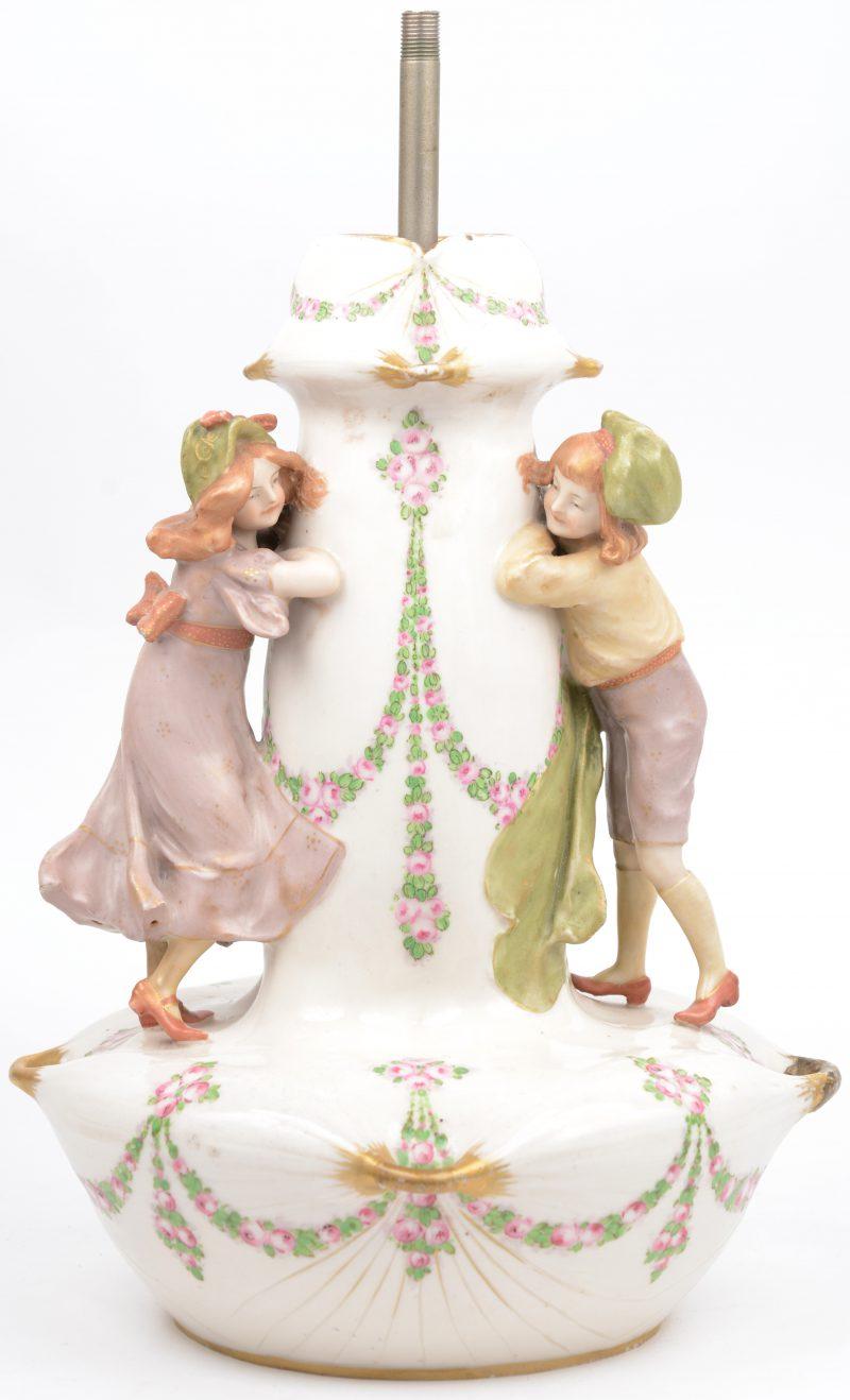 Een lampvoet van meerkleurig porselein, versierd met twee spelende meisjes. Onderaan gemerkt.