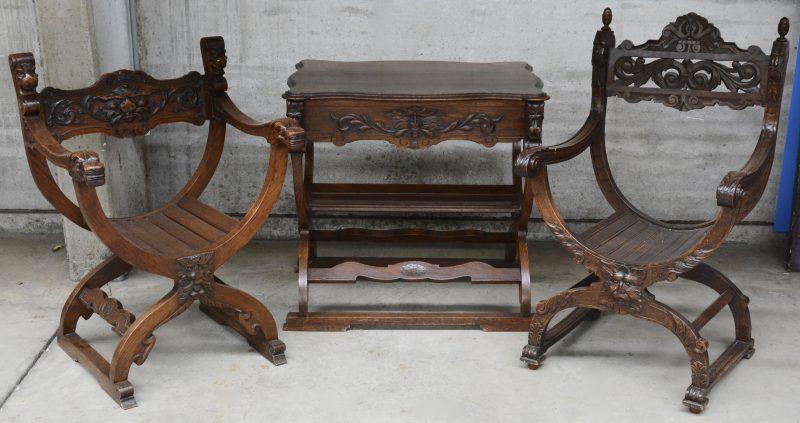 Een ensemble, bestaande uit twee verschillende dagobertstoelen en een gelijkaardig tafeltje van gebeeldhouwd eikenhout.