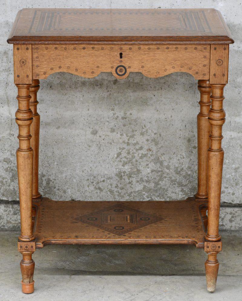 Een eikenhouten tafeltje met klapblad met binnenin een spiegel. Het geheeld versierd met ingelegde motieven van diverse houtsoorten. Spiegel gebarsten.