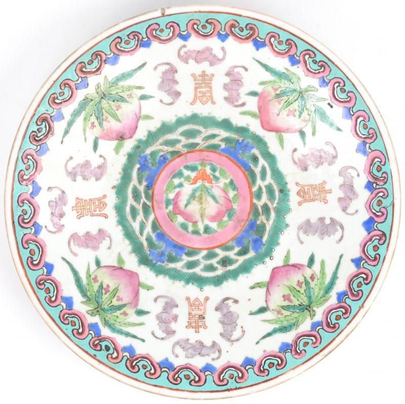Een schotel van Chinees porselein met een meerkleurig decor van vleermuizen en vruchten.
