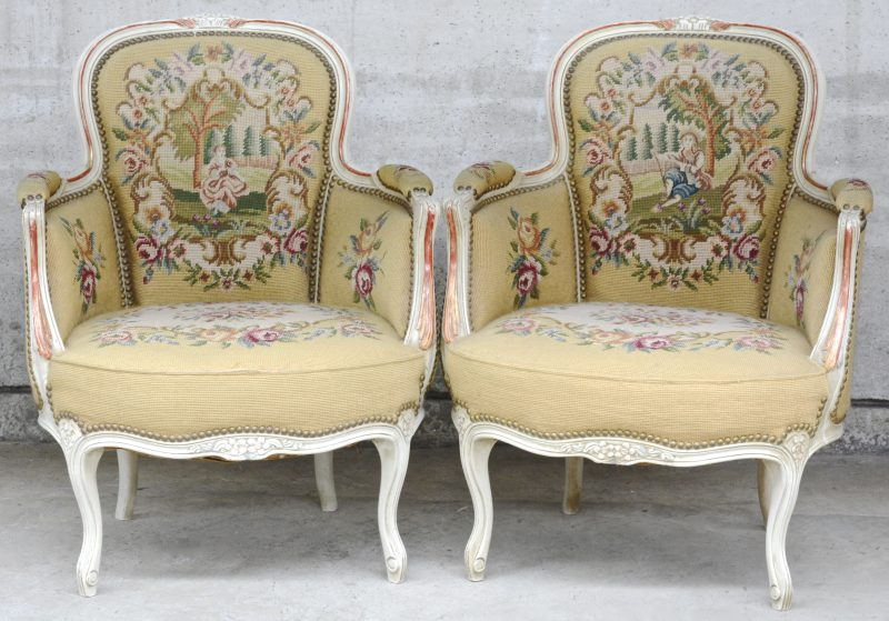 Een paar fauteuils in Lodewijk XV-stijl van wit- en roodgepatineerd hout en bekleed met naaldwerk.