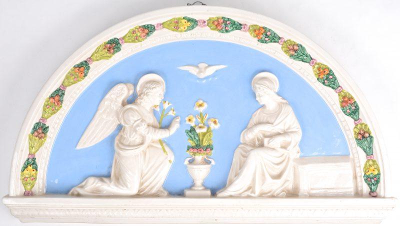Een halfrond timpaan van meerkleurig Italiaans aardewerk met een voorstelling van de verschijning van aartsengel Gabriël aan Maria.