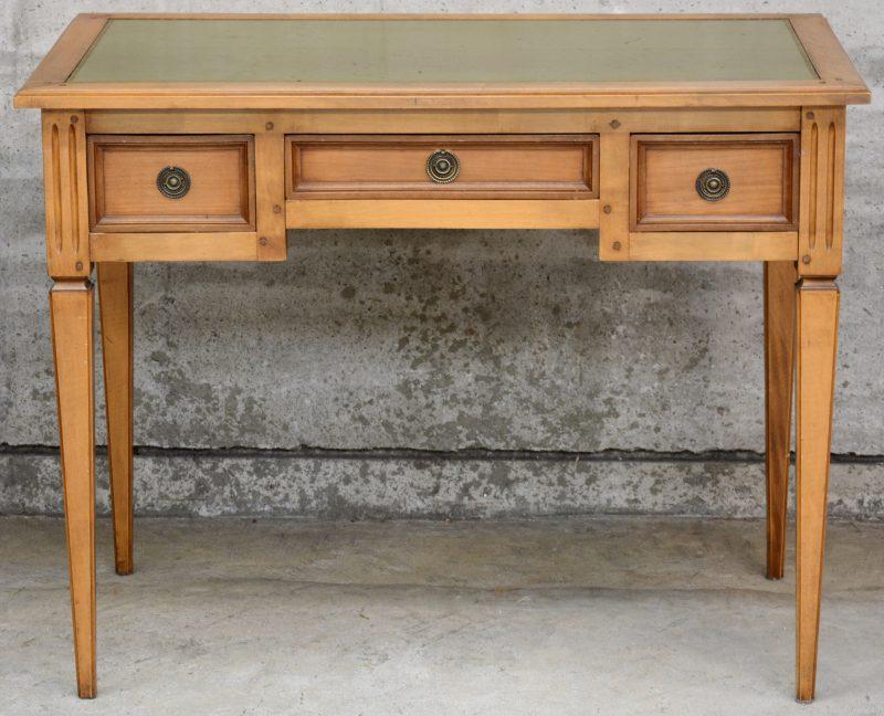 Een klein bureautje in Lodewijk XVI-stijl met drie laden en een kalfslederen blad.