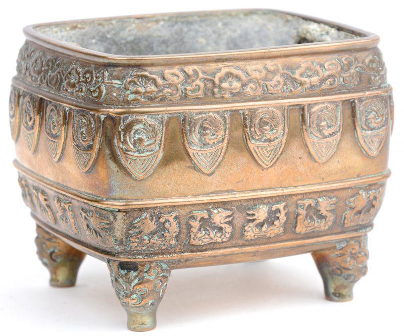Een klein Chinees plantenbakje van brons, versierd met motieven in reliëf.