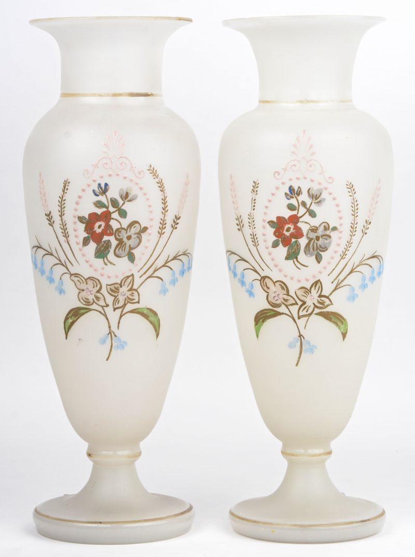 Een paar vazen van wit opaalglas met handgeschilderd bloemendecor. Eén met kleine randschilfer.