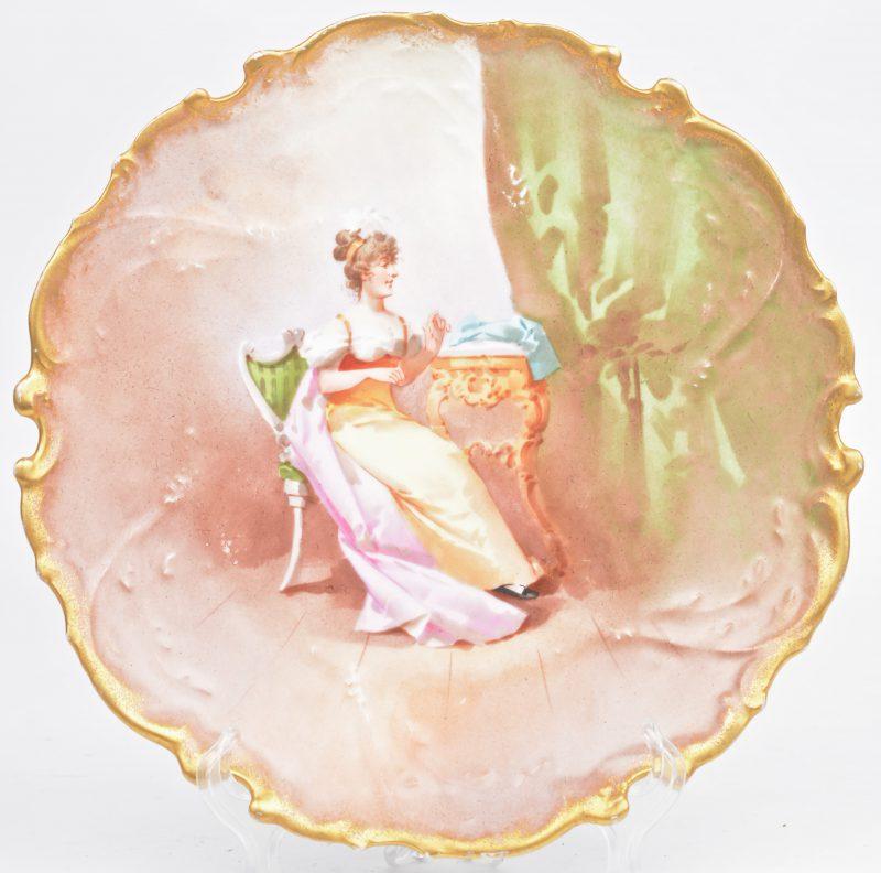 Een porseleinen sierbord met een handgeschilderd decor en vergulde rand in Lodewijk XV-stijl. Onderaan gemerkt.